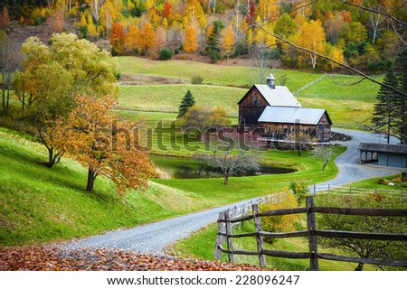Fall foliage, New England countryside at Woodstock, Vermont, farm in autumn landscape. Old wooden barn surrounded by colorful trees.