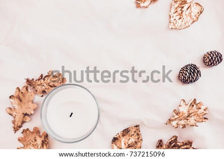 Fall golden leaves and candle from above on white bed sheets. Copy space for text