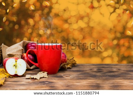 Fall harvest cornucopia. Cup of Hot apple tea for Autumn season warm drink. Copy space on wood background. Fresh start of the day.
