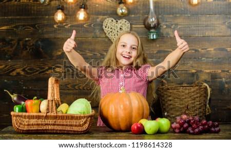 Fall harvest holiday. Elementary school fall festival idea. Celebrate harvest festival. Kid girl fresh vegetables harvest rustic style. Child presenting harvest vegetable garden wooden background.