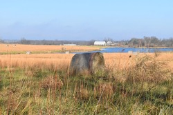 Fall hay field with a lake and a barn in the distance