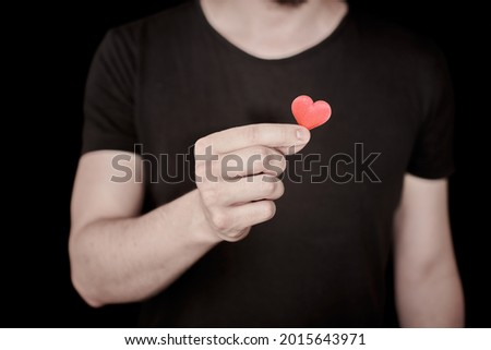 Fall in love concept. Give a heart, in love man. Heart as symbol of love in hand. Enamored lonely man, fall in love heartbreaker. Photo stock ©