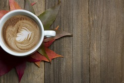 Fall latte sitting on wooden table with fall leaves