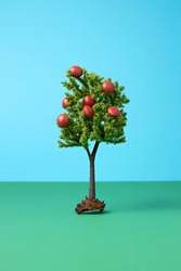 Fall layout made of miniature apple tree with red pills. Minimal Autumn concept.