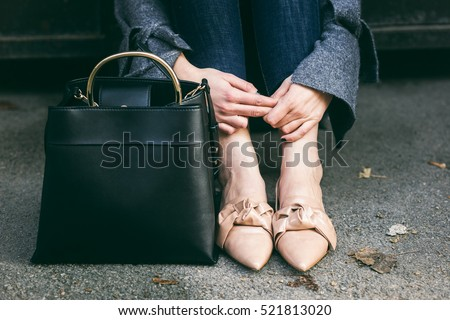 fall outfit fashion details, young stylish woman wearing oversized grey sweater, jeans and beige loafers. urban fashion blogger posing with a black trendy handbag.