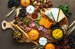 Fall party charcuterie board, top down view on rustic table with apetizer platter