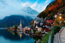 Fall scenery of Hallstatt at dawn, a peaceful lakeside village & a UNESCO heritage site in Salzkammergut region of Austria, with beautiful reflections in lake water & majestic mountains in background