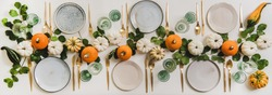 Fall table setting for celebration Thanksgiving or Friendsgiving day, family party or gathering. Flat-lay of plates, cutlery, glassware, colorful pumpkins and leaves over white background, top view