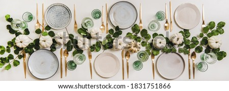 Fall table setting for celebration Thanksgiving or Friendsgiving day, family party or gathering. Flat-lay of plates, cutlery, glassware, pumpkins and leaves over plain white table background, top view