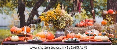 Fall themed holiday table setting arrangement for a seasonal party, glasses, pumpkins, candles, field flowers Foto d'archivio ©