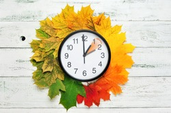 Fall time change still life with maple tree foliage and wall clock
