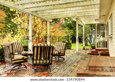 Fall trees and back porch with furniture.