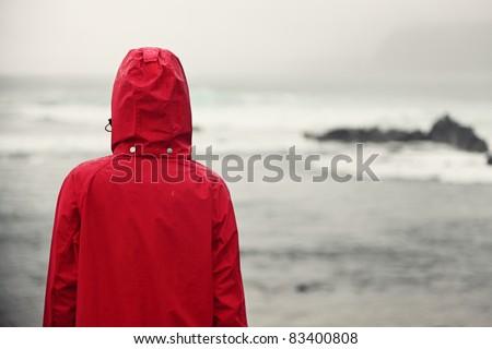 Fall woman in rain looking at ocean on grey day.