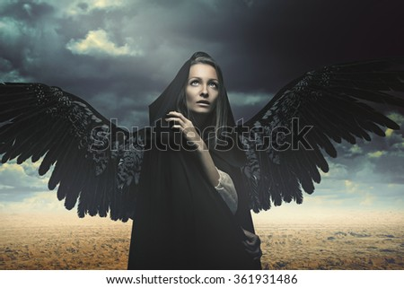 Stock Photo Fallen angel in a desert and stormy landscape. Fantasy and surreal