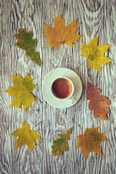 Fallen autumn leaves scattered around a cup of espresso on a wooden table, stylized