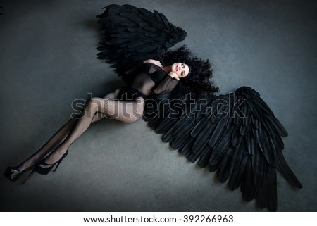 Stock Photo Fallen black angel with wings. Sexual woman
