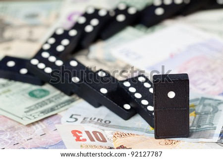 Fallen dominoes on pound, euro and dollar bank notes illustrating banking crisis or Brexit
