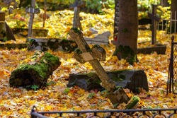 Fallen grave cross in an old abandoned cemetery on a sunny autumn day