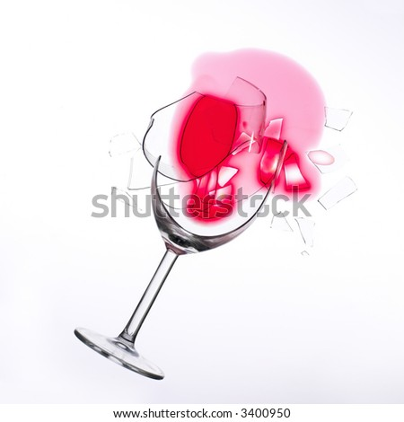 fallen wine glass with red wine in it and red stain on a white tablecloth