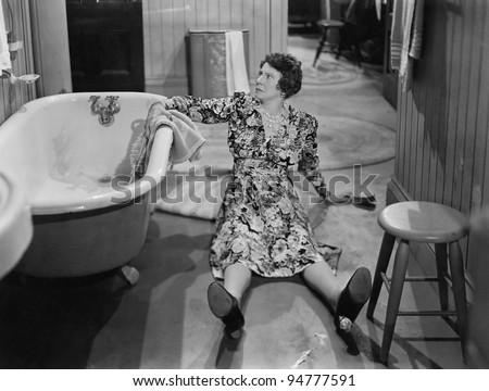 Fallen woman on floor next to bathtub