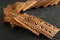 Fallen wooden domino tiles on dark grey table, closeup