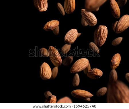 Falling almonds on black background. Popular tree nuts, healthy and nutritious ingredient.