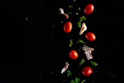 Falling bacon, cherry tomatoes, parsley on a black background with water drops, freeze in motion, cooking and recipe books, banner