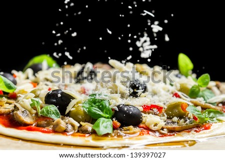 Falling cheese on a freshly prepared pizza with black olives