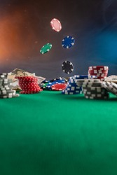 Falling chips on a poker table in a casino. Online poker bets.