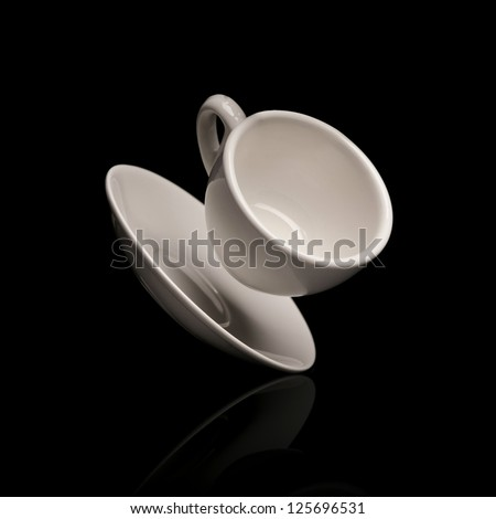 falling coffee cup with saucer isolated on black background