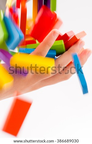 Falling colorful domino onto a  hand #386689030