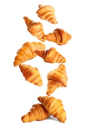 Falling delicious fresh baked croissants on white background. French pastry