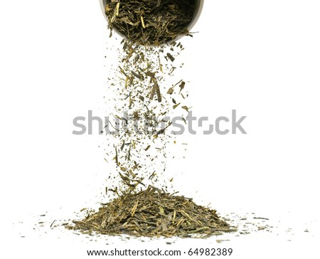 Falling dried green tea leaves over white background