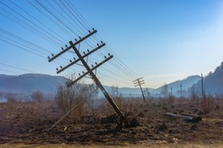 Falling electric pole in the field of the burned-down grass. The inclined pole is propped up by a branch. The grass in the field continues smokes. Mountains and  blue sky visible in the distance