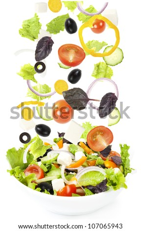 Falling fresh vegetable on plate with salad