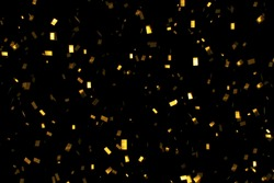 falling gold glitter foil confetti,  on black background, holiday and festive fun concept