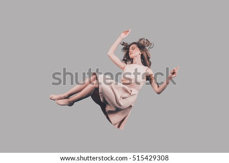 Falling in motion. Studio shot of attractive young woman hovering in air