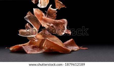 Falling jamon slices, dry italian prosciutto, raw pork ham isolated on black background with copy space Foto stock ©