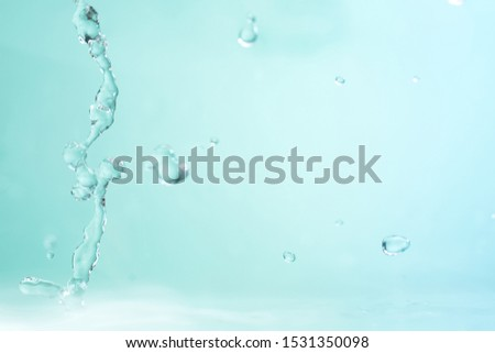 Falling jets and drops of clear, clear blue water. Close-up.