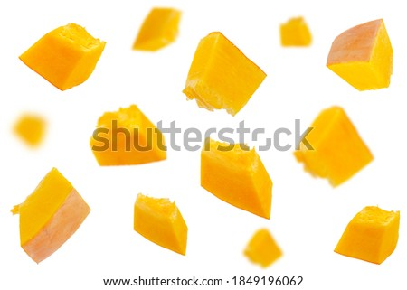 Falling pumpkin slices isolated on a white background, selective focus. Set of pumpkin slices in the air. Pumpkin slices fall. Pumpkin slices in the air on a white background.