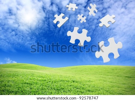 falling puzzle pieces on a green field landscape - stock photo
