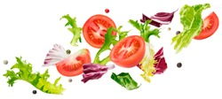 Falling salad of leaves with rucola, lettuce, radicchio, romano green frize and tomatoes isolated on white background