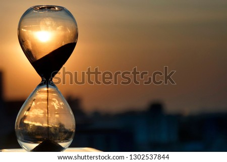Falling sand in a hourglass with city silhouette and twilight sky background