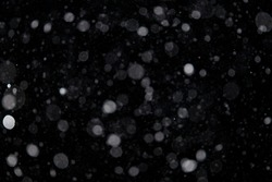 Falling snow out of focus on the black background. Snowfall for use as a texture layer in your project.