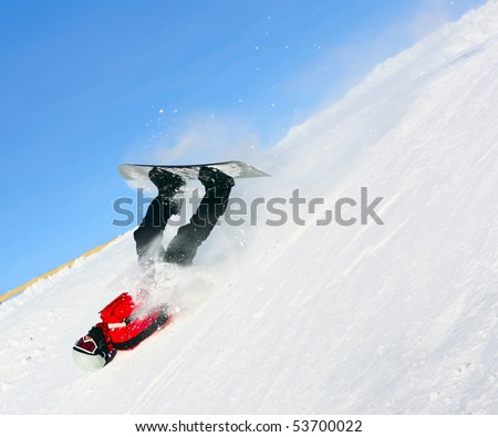 Falling snowboard rider in red suit