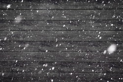 Falling snowflakes on a wooden background. The texture of the snow. Snowstorm. Element for the design. The bokeh effect. Wooden boards texture.