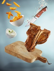 Falling T-bone steak meal with cutting board suspended in the air with a bowl of fried potato wedges, tzatziki dip, a sharp knife, salt and pepper over a graduated grey background with shadow below