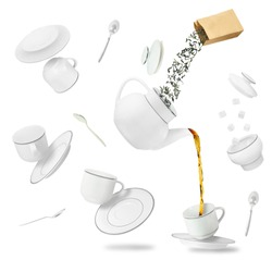 Falling tea leaves, cups, saucers and pot isolated on white background. Concept of flying tea party