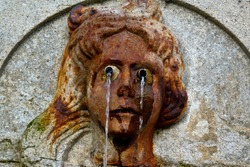 falling water from a stone woman's head sculpture