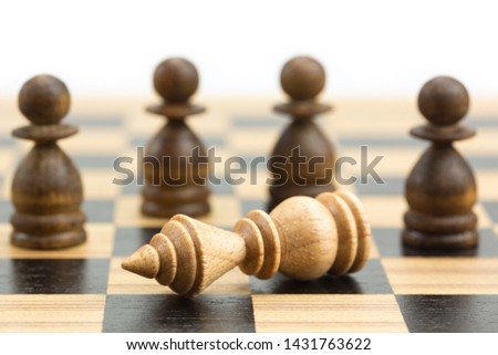 Falling white king has threatened with capture by masses of pawns on wooden chess board, checkmate concept in chess game #1431763622